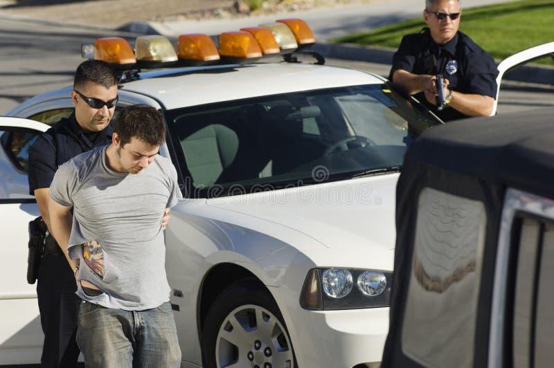 Полицейский арестовывая молодого человека стоковые фото
