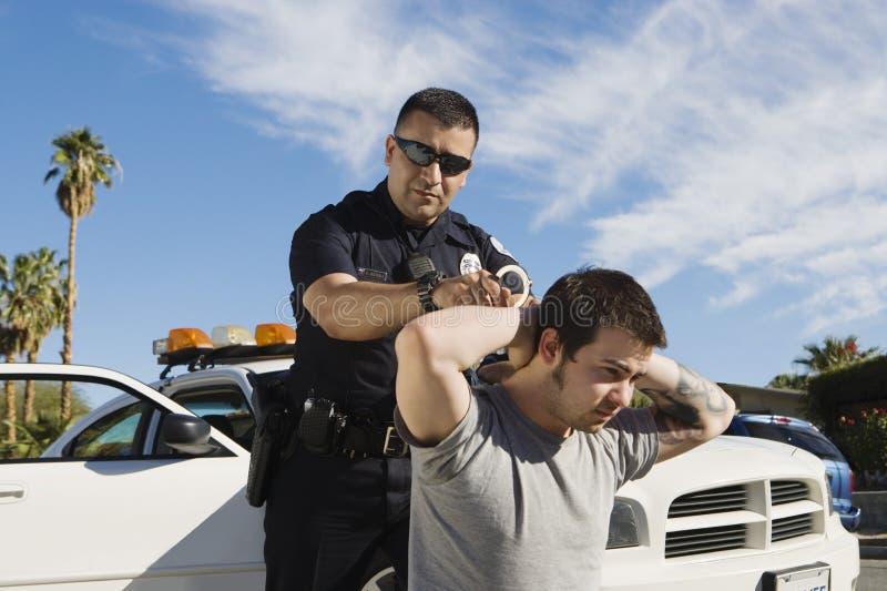 Полицейский арестовывая молодого человека стоковое изображение