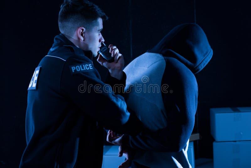 Полицейский арестовывая нарушителя закона стоковое изображение