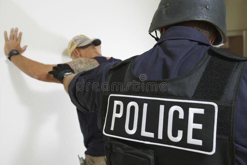 Полицейский арестовывая человека стоковое изображение