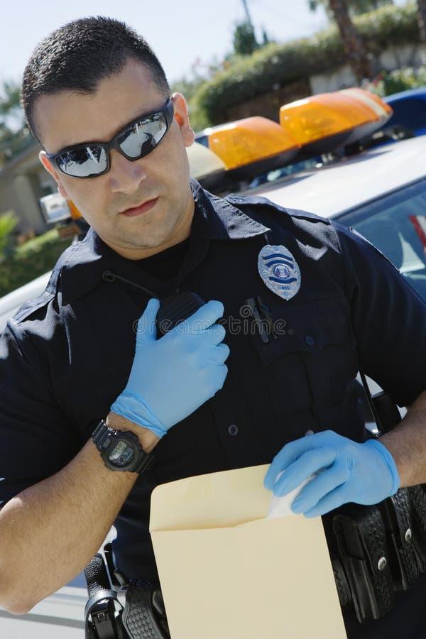 Полицейский используя двухстороннее радио стоковые изображения rf