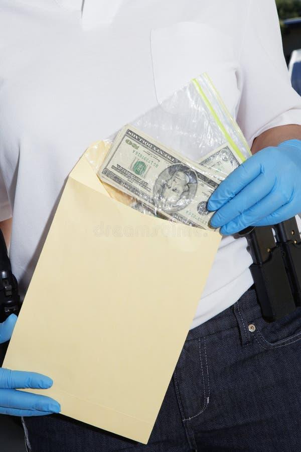 Полицейский кладя деньги в конверт доказательства стоковые изображения rf