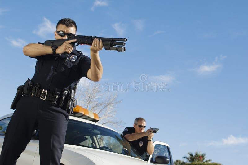 Полицейский направляя корокоствольное оружие стоковые фотографии rf