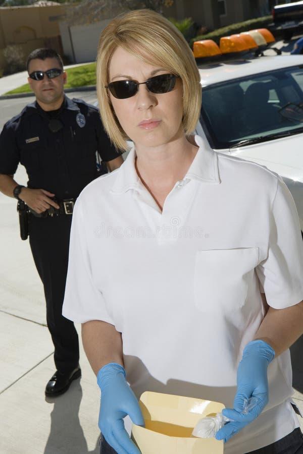 Полицейский с конвертом доказательства стоковая фотография rf