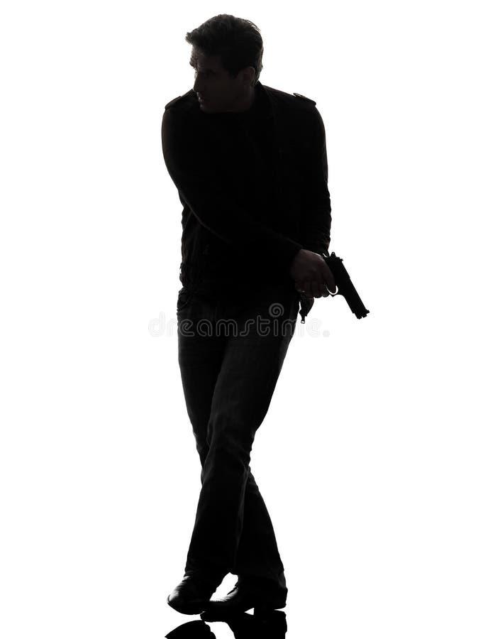 Полицейский убийцы человека держа силуэт оружия идя стоковые изображения