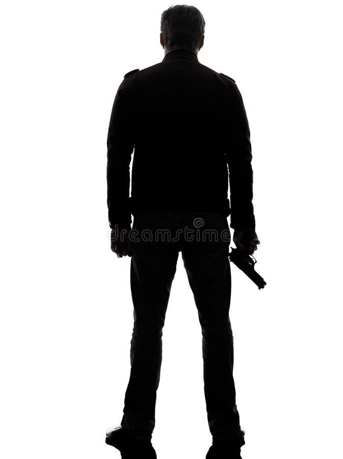 Полицейский убийцы человека держа силуэт оружия идя стоковые фото
