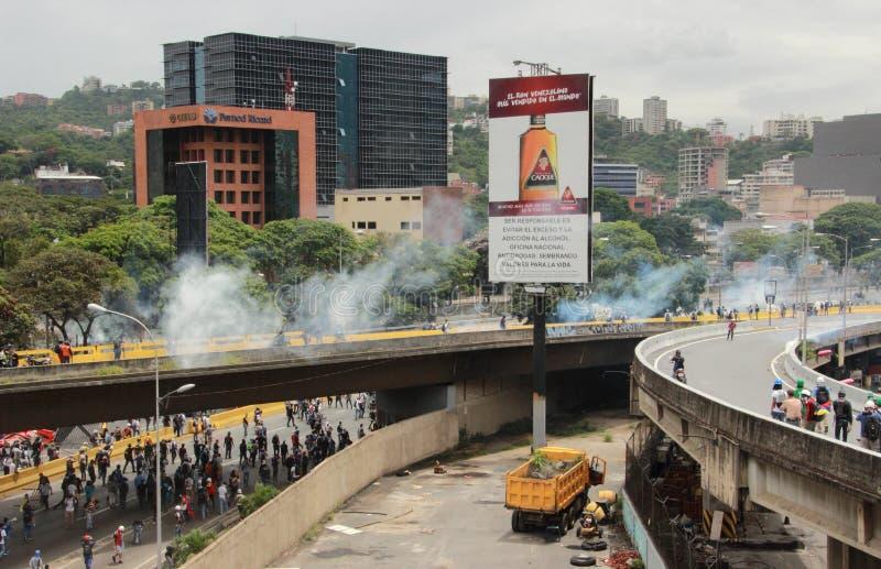 Полиция использовала слезоточивый газ и резиновые пули в антипровительственном протесте в Каракасе Венесуэле мае 2017 стоковая фотография