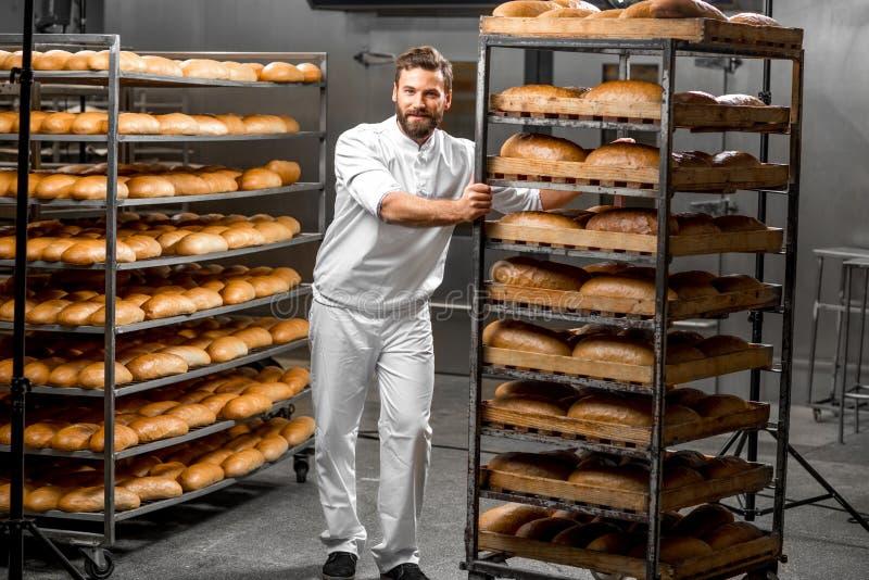 Полки нося работника с хлебом стоковое фото rf