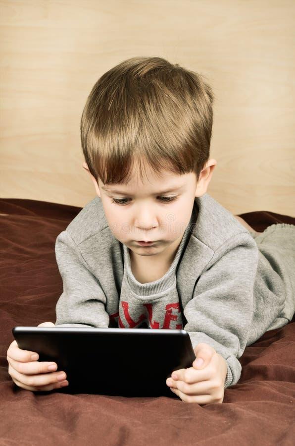 Подкрашиванный мальчик изображения лежа на кровати и играх на таблетке стоковые фотографии rf