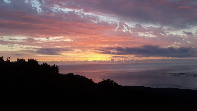 По мере того как солнце идет вниз и световые лучи вперед над океаном стоковое фото rf