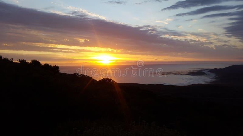 По мере того как солнце идет вниз и световые лучи вперед над океаном стоковые фотографии rf
