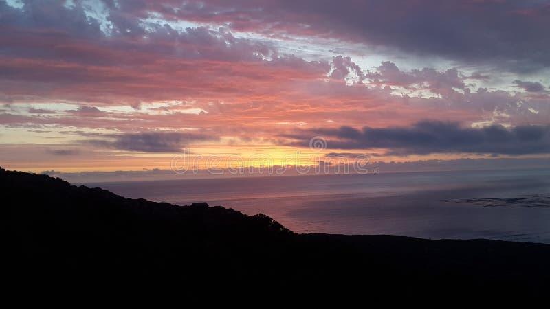 По мере того как солнце идет вниз и световые лучи вперед над океаном стоковое изображение rf