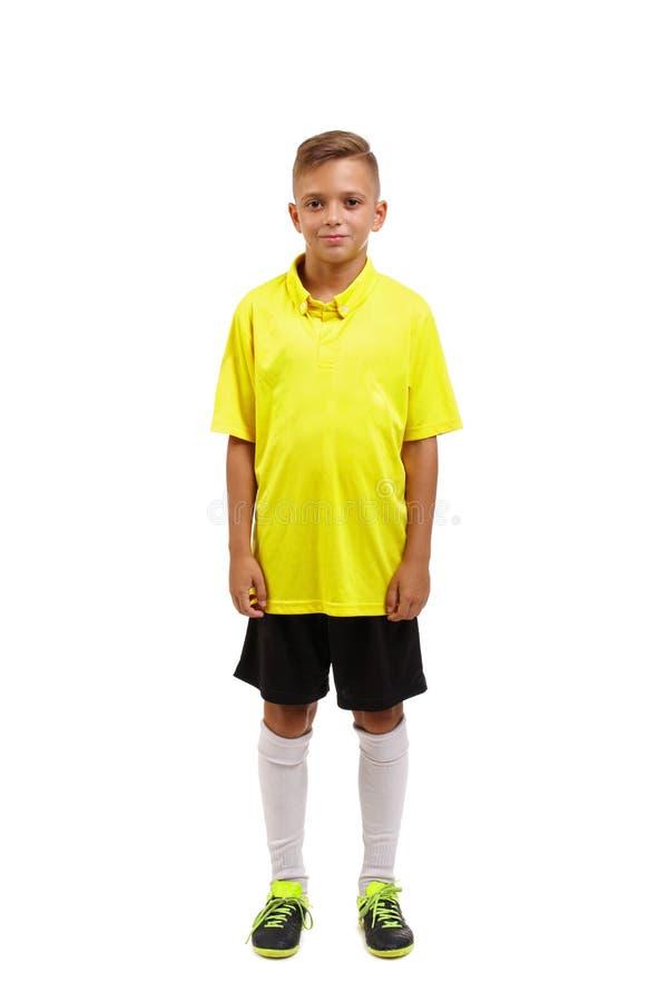 Полная высота милого мальчика в желтой футболке, черных шортах и белых носках колена изолированных на белой предпосылке стоковые изображения