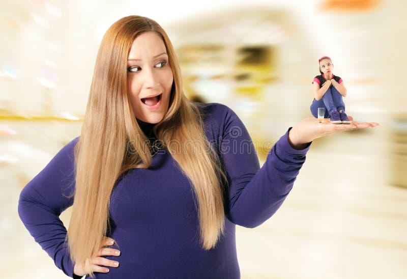 Полная женщина держа тонкое смешное стоковая фотография