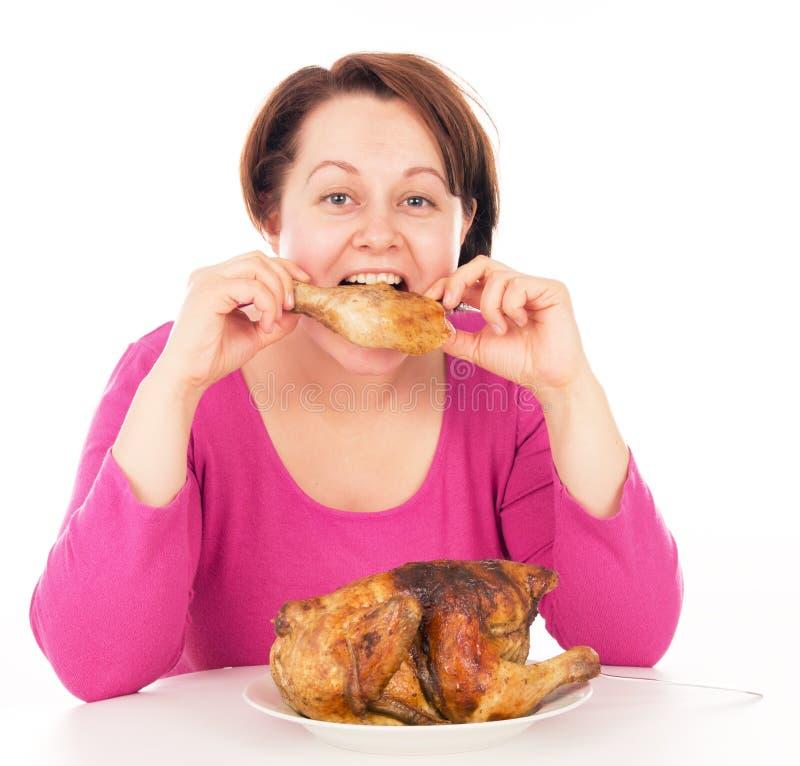 Полная женщина жадно поглощая часть цыпленка стоковое фото rf