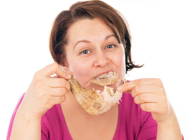 Полная женщина жадно поглощая часть цыпленка стоковые изображения