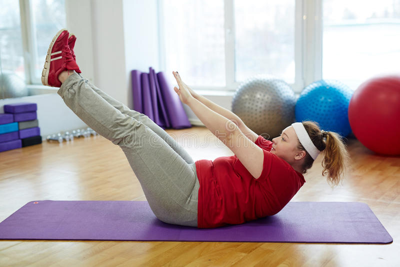 Полная женщина разрабатывая крепко в студии фитнеса стоковые изображения rf