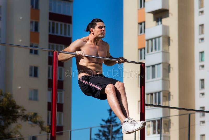 Подниматься мощного спортсмена тяжелый на бар в внешнем в городе стоковая фотография rf