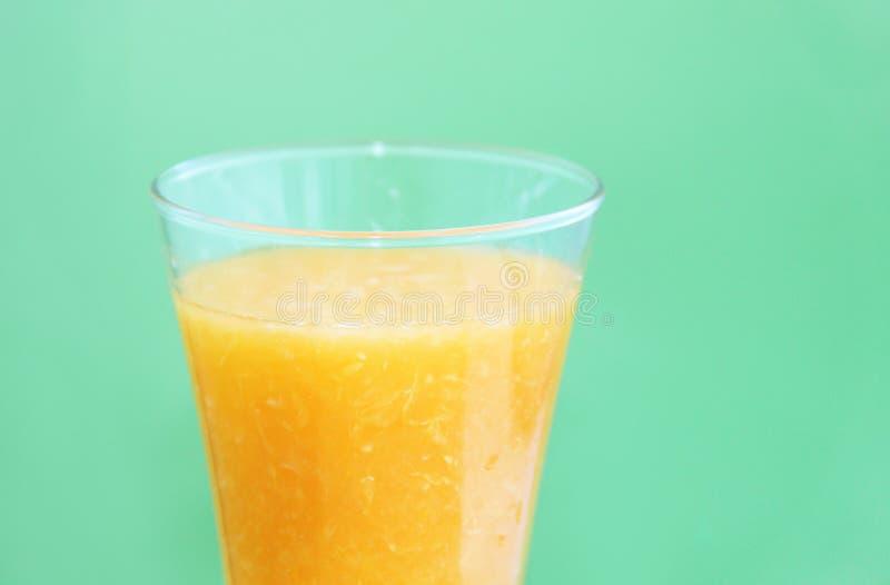 Полное стекло апельсинового сока на зеленой предпосылке стоковые фото