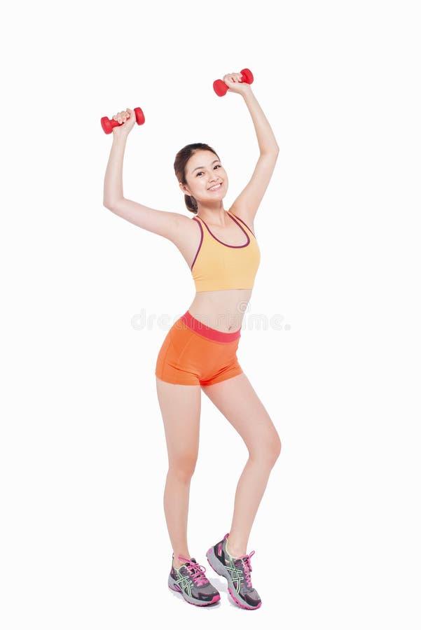 Полное тело молодой жизнерадостной усмехаясь женщины с гантелью изолят стоковое фото rf