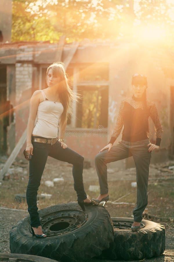 Полное тело сняло 2 женщин стоя на покрышки outdoors стоковая фотография
