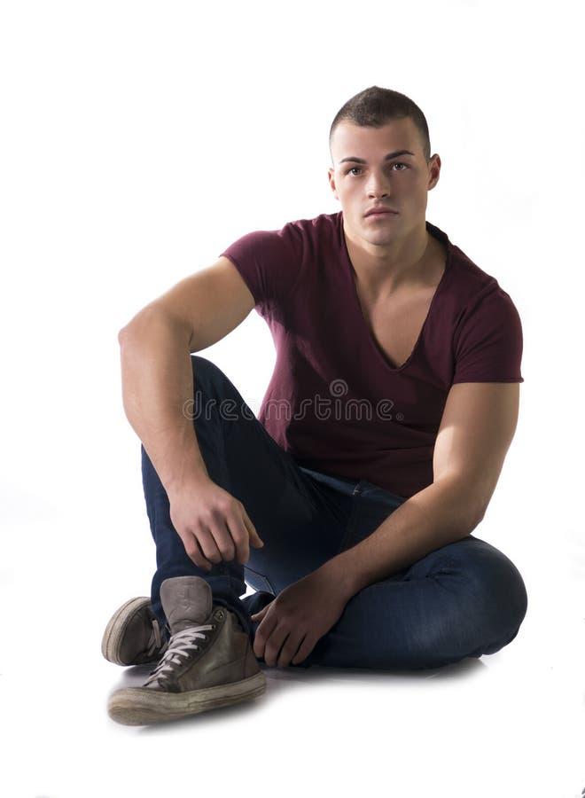 Полное тело сняло красивого молодого человека сидя на поле стоковая фотография