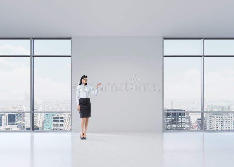 Полнометражная девушка брюнет в официально одежды указывает вне что-то ее рукой на белой стене стоковое изображение rf