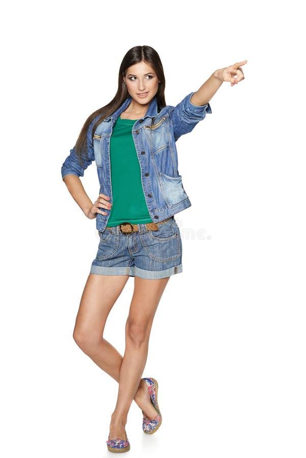 Полнометражная девушка джинсовой ткани моды указывая к стороне стоковое изображение