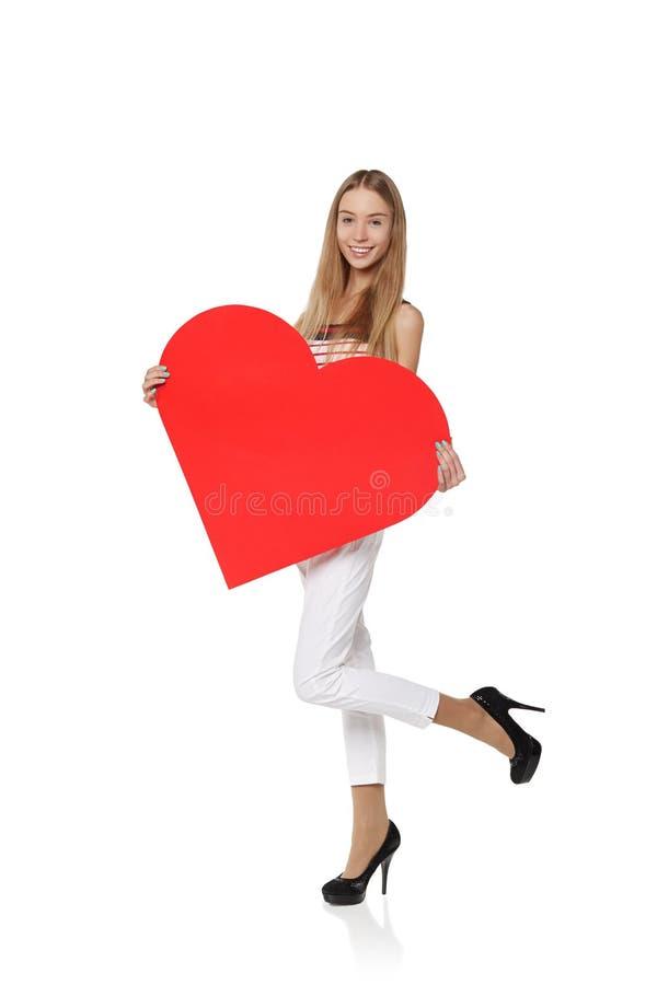 Полнометражная девушка задерживая красное сердце картона, ioslated на w стоковые изображения