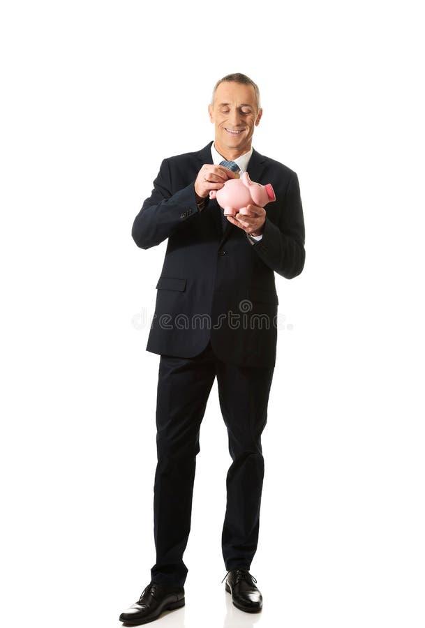 Полнометражный жизнерадостный бизнесмен держа piggybank стоковое изображение