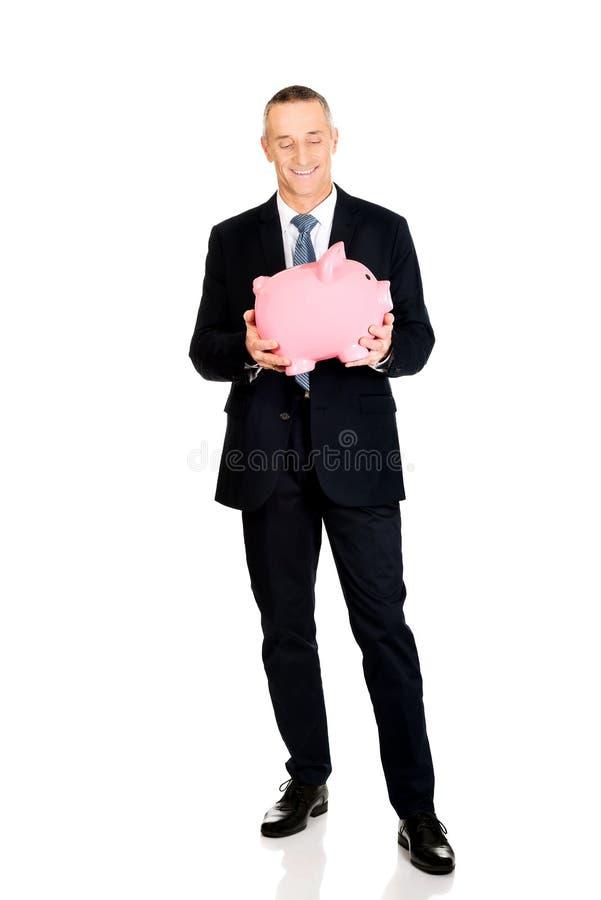 Полнометражный жизнерадостный бизнесмен держа piggybank стоковые изображения rf