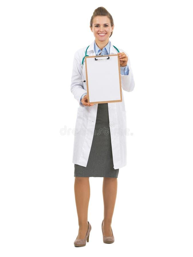 Полнометражный портрет женщины доктора показывая пустую доску сзажимом для бумаги стоковое фото rf