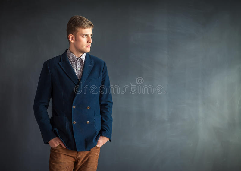 Полнометражный портрет красивого серьезного человека стоя против gr стоковое фото rf