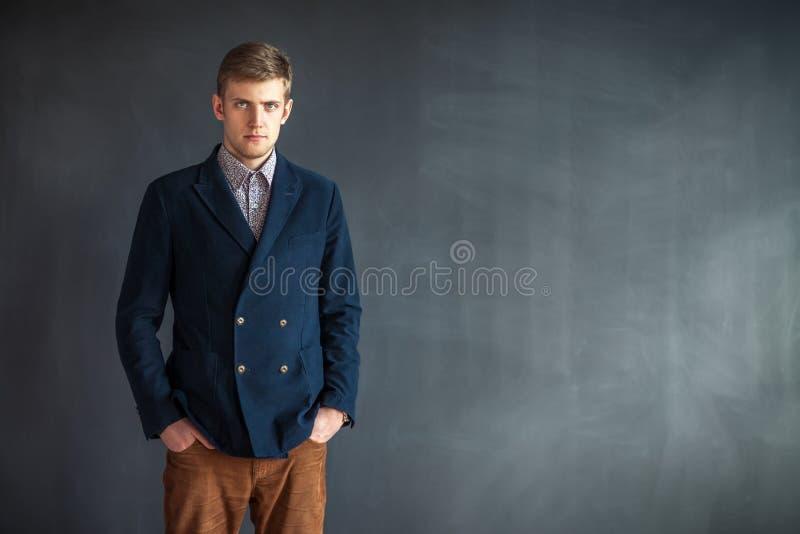 Полнометражный портрет красивого серьезного человека стоя против gr стоковое изображение