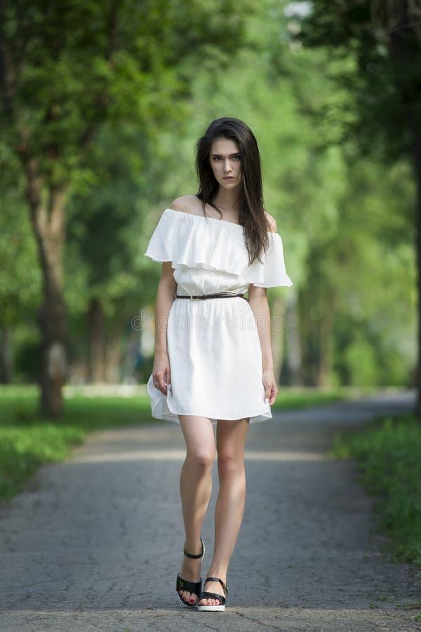 Полнометражный портрет красивой молодой кавказской женщины в белом платье с открытыми плечами, чистой кожей, длинными волосами и  стоковые фото