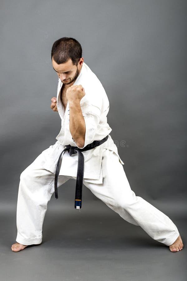 Полнометражный портрет молодого человека в белом кимоно и черном поясе стоковое фото rf