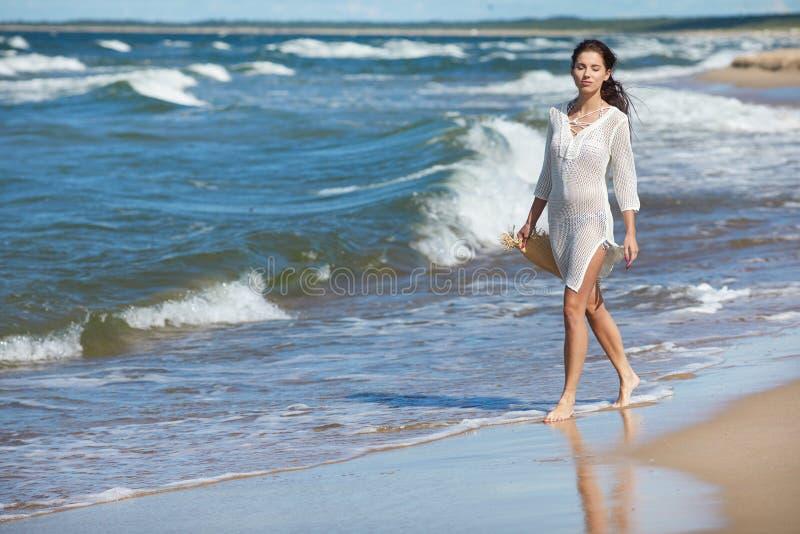 Полнометражный портрет молодой женщины в шортах идя на b стоковые изображения rf