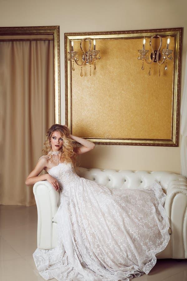 Полнометражный портрет невесты красоты в белом платье сидя в s стоковое фото rf
