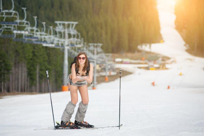 Полнометражный портрет счастливого нагого женского лыжника Усмехаясь девушка имеет потеху на снежном наклоне стоковая фотография rf