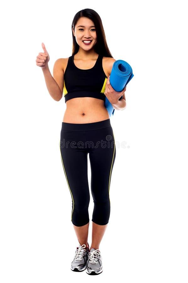 Полнометражный портрет тонкой девушки держа голубую циновку стоковые изображения