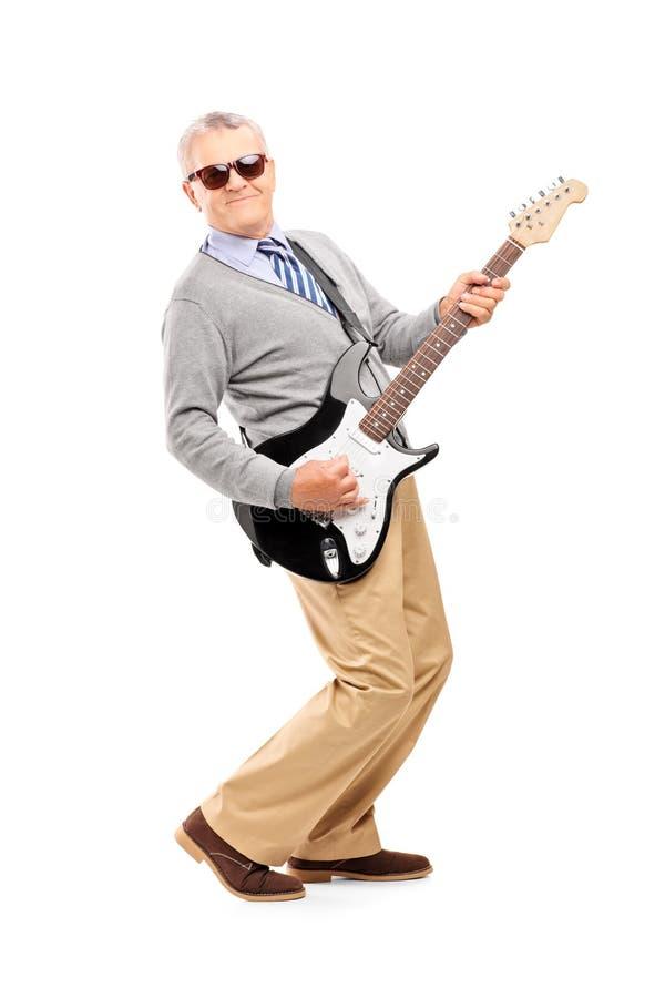 Полнометражный портрет усмехаясь зрелого человека играя гитару стоковые изображения
