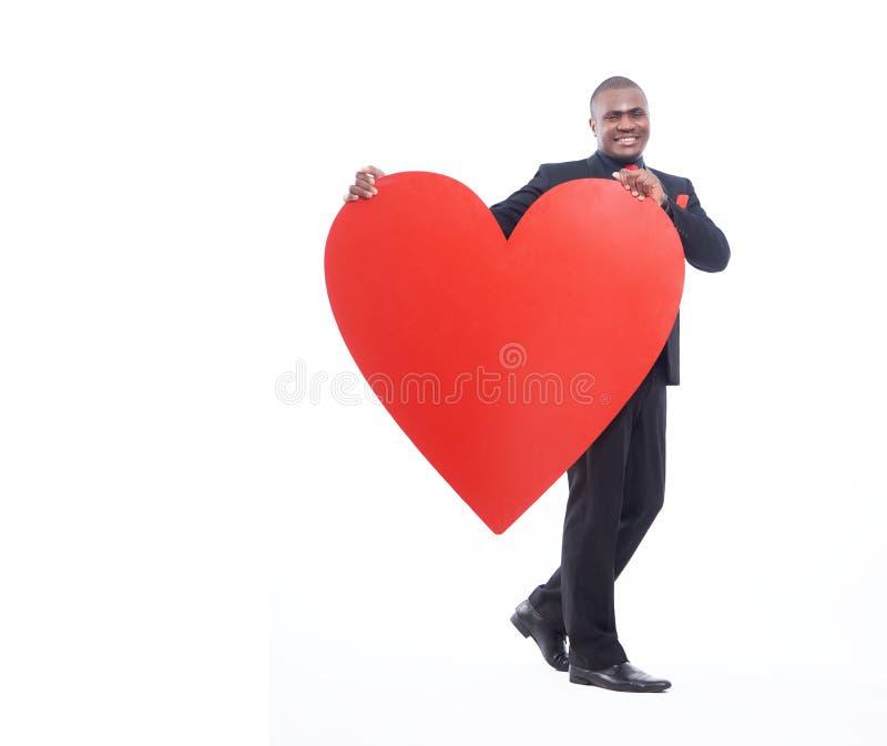 Полнометражный портрет человека держа большое сердце стоковая фотография rf