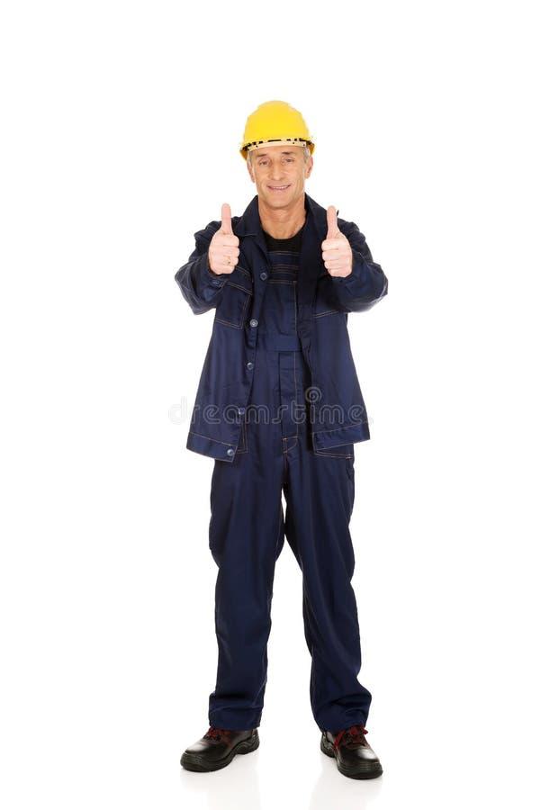 Полнометражный ремонтник показывая большие пальцы руки вверх стоковое изображение rf