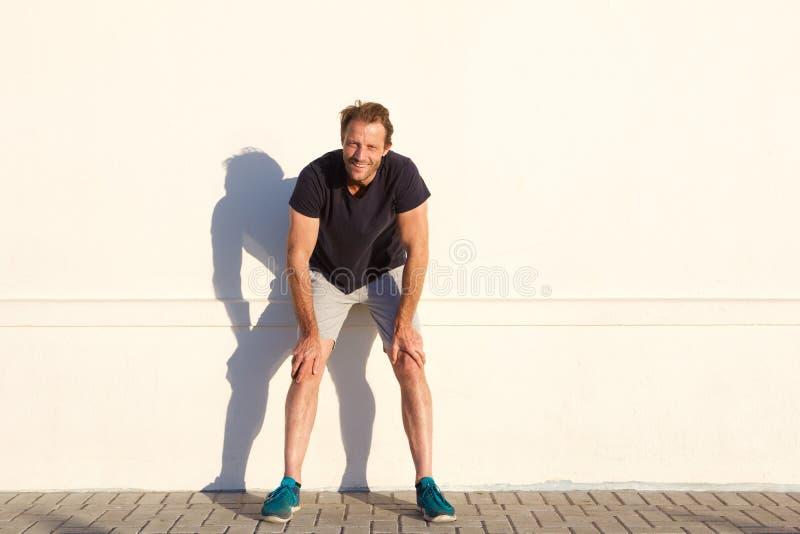 Полнометражный человек спорт отдыхая против стены стоковая фотография rf