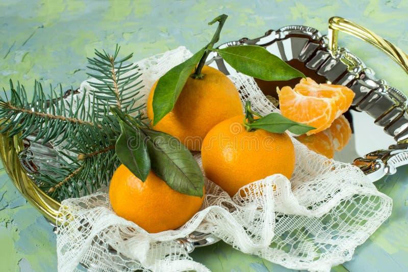 Поднос с tangerines, елевыми ветвями и кружевной салфеткой стоковое фото