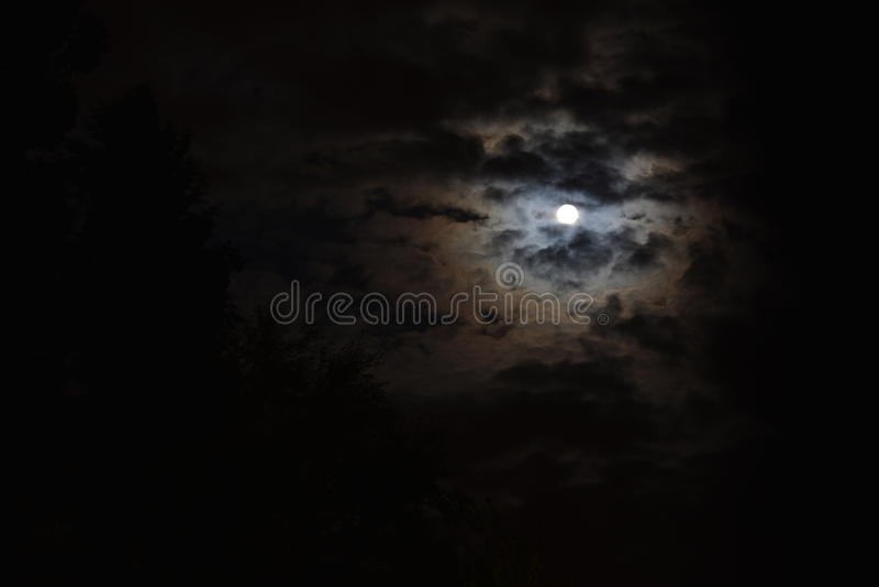 Полнолуние с красивыми освещенными облаками стоковое изображение