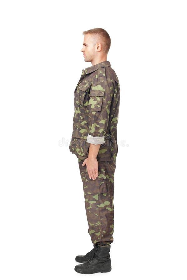 Полный взгляд со стороны тела солдата армии стоя в внимании стоковые фото