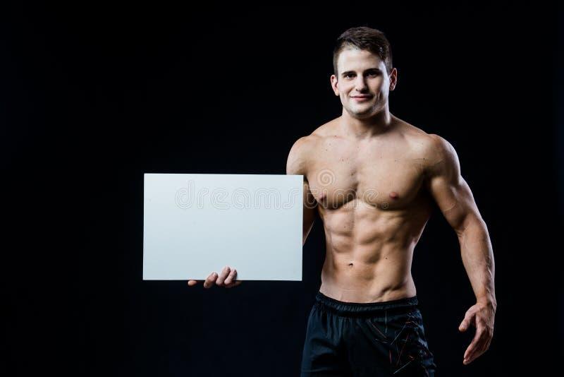 Полный культурист тела при пустой белый плакат изолированный на черной предпосылке Красивый мышечный человек держа серую доску стоковое изображение rf
