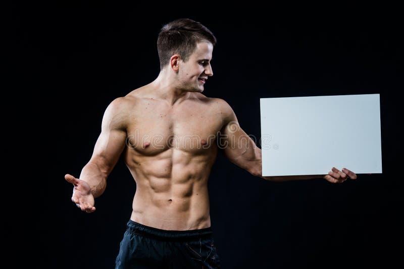 Полный культурист тела при пустой белый плакат изолированный на черной предпосылке Красивый мышечный человек держа серую доску стоковые изображения rf