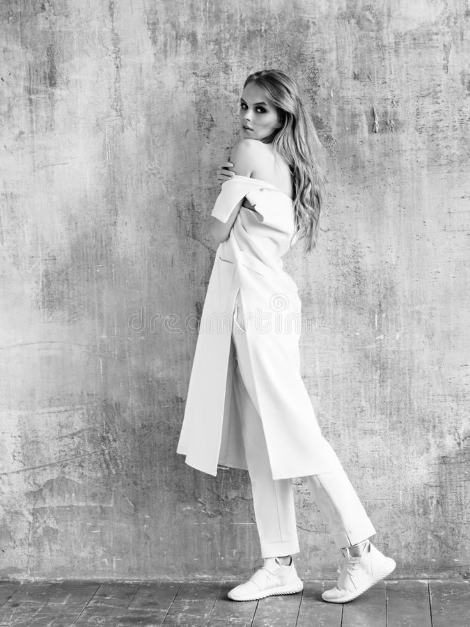 Полный портрет пальто, брюк и тапок дизайна женщины моды нося белых стоковое изображение rf